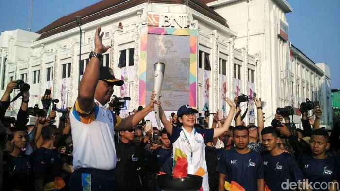 Danlanal Yogyakarta Arya Delano menyerahkan api obor Asian Games kepada Direktur Bisnis Ritel BNI Tambok P Setyawati.