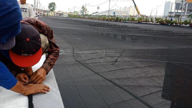 Pekerja memasang waring di Kali Sentiong