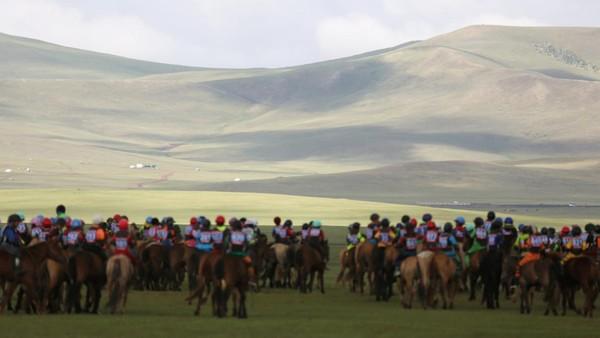 Festival Naadam adalah tradisi masyarakat Mongolia yang telah dilakukan turun-temurun. Di festival ini, para orang tua mengikut sertakan anaknya dalam lomba pacuan kuda. (REUTERS/B. Rentsendorj)