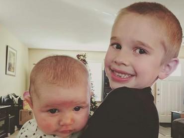 Hmm, si adik kayaknya tegang banget ya digendong kakaknya? He-he-he. (Foto: instagram/@onlytheescentials)