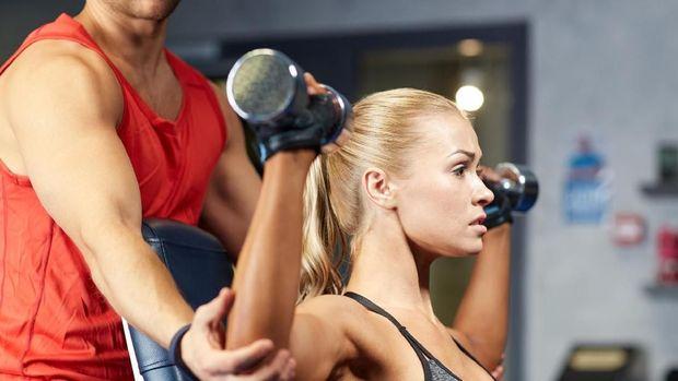 Ilustrasi seorang instruktur melakukan spotting atau membantu klien melakukan angkat beban.