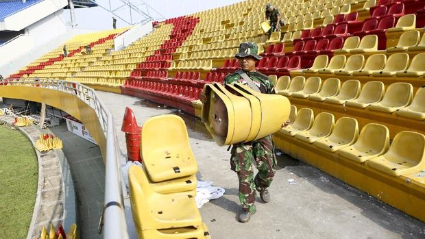 Anggota TNI dari satuan Yon Zikon 12 / Karana Jaya membantu proses perbaikan Stadion Jakabaring pada Senin (23/7).