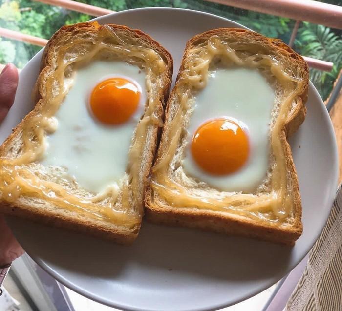Ini cara paling praktis sajikan roti plus telur. Buat sedikit cekungan pada roti tawar lalu pecahkan telur di cekungannya dan panggang sebentar hingga telur beku. Foto: Instagram @restaurant.insta.marketing