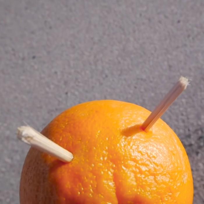 Lewat alat peraga jeruk Kurtis menjelaskan bila bumi bulat maka dua tongkat kayu tersebut bila ditaruh sejajar dengan jarak tertentu di bawah matahari seharusnya akan menghasilkan bayangan dengan tinggi yang berbeda. (Foto: Youtube/Kurtis Baute)