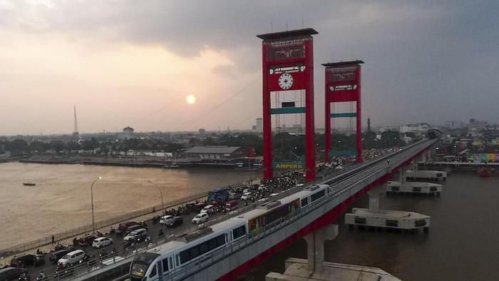 Rangkaian Light Rail Transit (LRT) Palembang melintas di atas Sungai Musi, Palembang, Sumatra Selatan, Senin (23/7). Operasional LRT Palembang dengan penumpang dilakukan sejauh 24,5 km, dari Stasiun Dekranasda Jakabaring (DJKA) sampai Stasiun Bandara SMB II. Operasional tersebut masih terbatas stakeholder seperti petugas LRT, Dinas Perhubungan, dan instansi terkait lainnya. ANTARA FOTO/Nova Wahyudi/kye/18