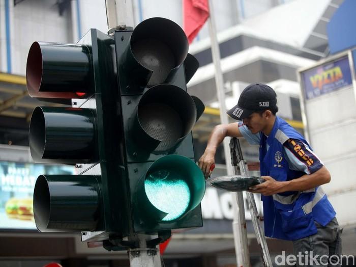 Sejumlah petugas Dinas Perhubungan tengah melakukan perbaikan dan perawatan lampu lalu lintas di kawasan Sarinah, Jakarta.