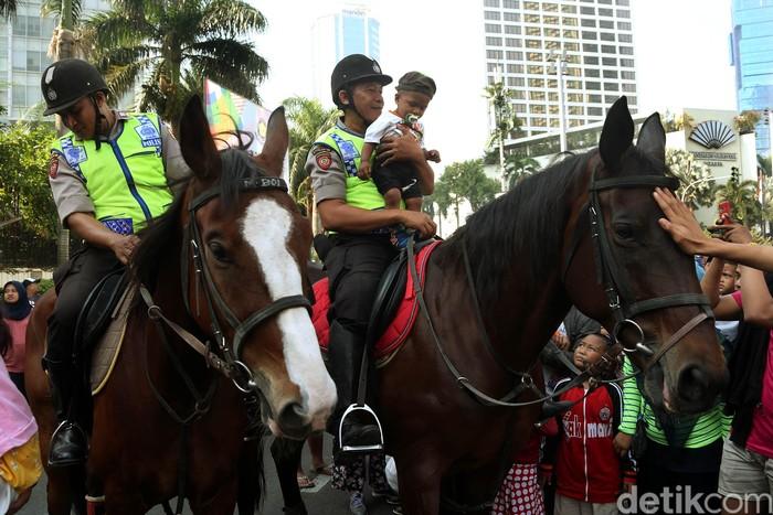 Polisi dari Direktorat Polisi Satwa Mabes Polri yang menunggangi kuda untuk mengawasi keamanan FCD, memperbolehkan anak-anak menaiki kuda tersebut.