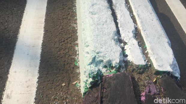 Bercak cat warna-warni masih terlihat di pembatas jalan kawasan Pasar Rebo
