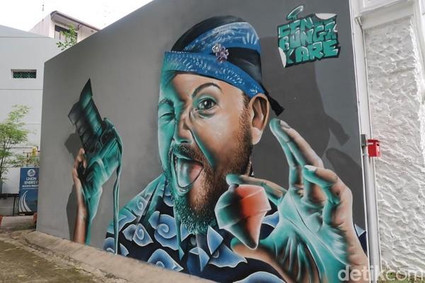 Selain itu, ada pula mural hasil kolaborasi seniman Indonesia dan Singapore. Mural ini berada di samping vintage camera museum. Gambarnya adalah seorang pria yang menggunakan blangkon dan baju batik. Di sampingnya terdapat nama seniman, Cena, Bunga and Kare. (Bonauli/detikTravel)