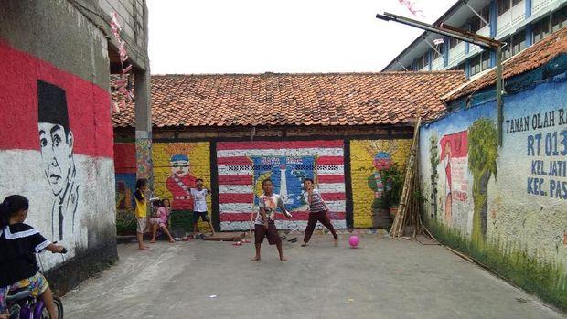 Anak-anak bermain di taman olah raga dan balai warga yang sudah dilukis