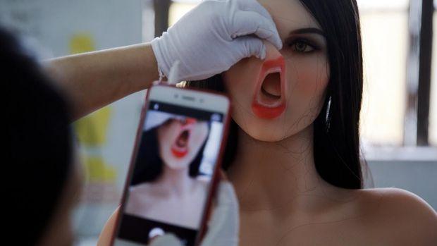 Petugas pabrik sedang memasang wajah robot seks AI (Foto: Aly Song/REUTERS)
