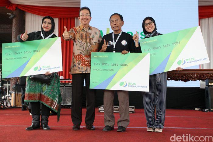 Direktur Kepesertaan BPJS Ketenagakerjaan, E. Ilyas Lubis secara simbolis memberikan kartu anggota BPJS Ketenagakerjaan kepada para pelaku usaha kecil menengah (UKM), Jakarta, Sabtu (4/8/2018).