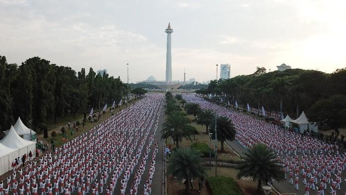 Ribuan warga melakukan senam poco-poco saat pemecahan rekor dunia senam massal poco-poco di Monas, Jakarta, Minggu (5/8). Kegiatan dalam rangka menyambut Asian Games 2018 itu diikuti 65 ribu peserta dari berbagai kalangan. ANTARA FOTO/Akbar Nugroho Gumay/ama/18
