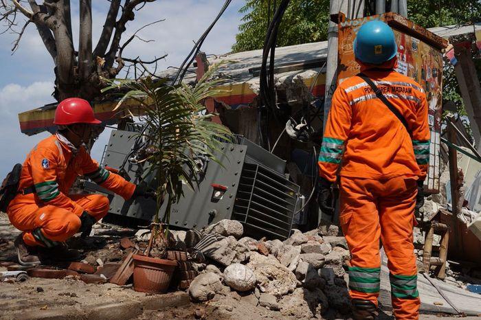 Petugas mengecek trafo yang tertimpa reruntuhan bangunan. Dian/Humas PLN Pusat.