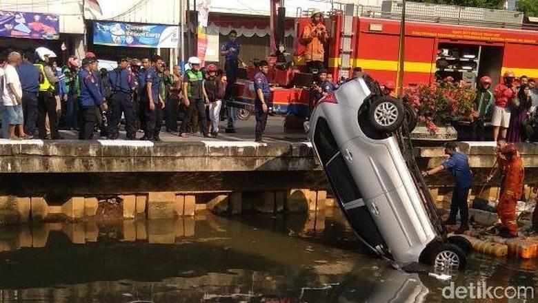 Damkar Evakuasi Mobil Nyemplung di Kali Glodok