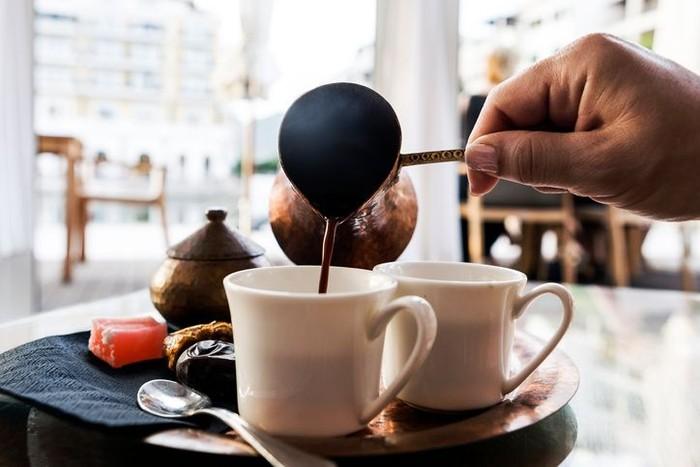 Orang Turki menikmati kopi dengan ritual tradisional. Bubuk kopi bersama air dan kadang gula direbus dalam cezve, berupa teko berbahan tembaga atau kuningan dengan gagang ramping. Kopi lalu disajikan dalam cangkir kecil bersama kudapan manis. Foto: Istock