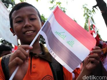 Salah satu anak sekolah membawa bendera Irak saat menyambut pawai obor Asian Games. (Foto: Lamhot Aritonang/detikcom)