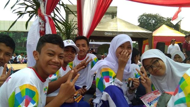 Sejumlah siswa SMP ikut memeriahkan kedatangan api obor dengan membawa bendera peserta Asian Games