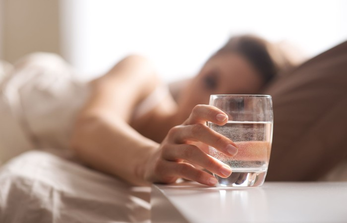 Close up of womans hand taking a glass of water