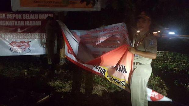 Satpol PP Depok saat menurunkan spanduk penolakan Neno Warisman di GDC
