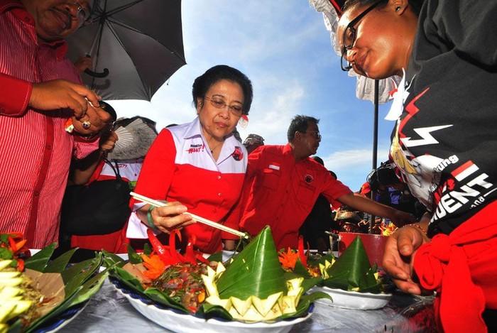 Diah Permata Megawati Setiawati Soekarnoputri atau akrab disapa Megawati. Merupakan mantan presiden RI ke-5. Ini posenya saat mencicipi tumpeng dengan lauk komplet. Foto: Zabur Karuru.