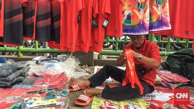 Para pelapak kecil memanfaatkan tempat-tempat umum untuk menjajakan dagangan mereka selama laga Timnas Indonesia bertanding di Asiang Games 2018. (