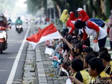 Anak-anak menunggu pawai obor di Jakarta sambil duduk di trotoar. (Foto:Pradita Utama/detikcom)
