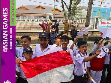 Para pelajar Bandung memeriahkan pawai obor Asian Games 2018 dengan membentangkan bendera Merah Putih. (Foto: Instagram @asiangames2018).