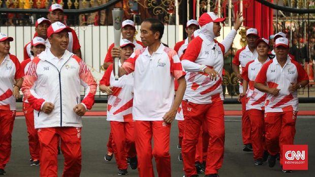 Presiden Jokowi tersenyum kepada Menpora Imam Nahrawi saat mengetahui api obor Asian Games 2018 sempat padam. (