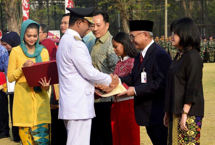 Direktur Kepatuhan Bank DKI, Budi Mulyo Utomo (dua kanan) menerima penghargaan yang diberikan oleh Gubernur DKI Jakarta Anies Baswedan usai upacara kemerdekaan RI ke 73 tahun di Jakarta, Jumat (17/8/2018). Foto: dok. Pemprov DKI