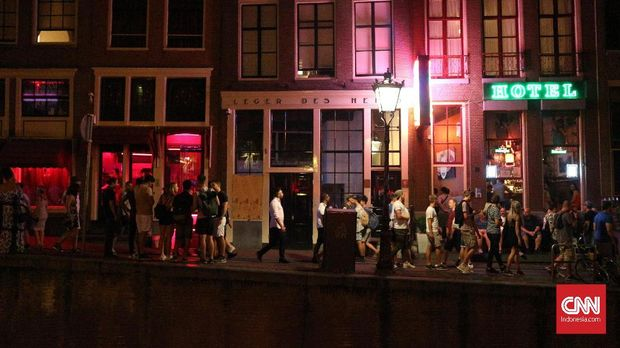 Para PSK menjajakan diri melalui pintu berkaca di red light district De Wallen, Amsterdam.