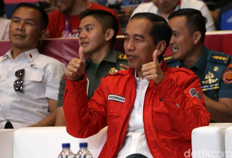 Jokowi saat mengenakan jaket merah anak motor. Foto: Agung Pambudhy