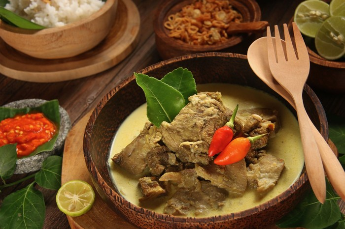 Gulai Kambing, the traditional mutton curry soup  popular in Central and East Java. Mutton chunks braised in coconut milk and curry spices. The soup is served in a shallow wooden bowl with red chili paste aside.