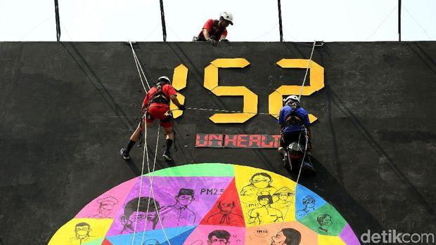 Para relawan Greenpeace memasang spanduk raksasa soal kualitas udara di Jakarta.