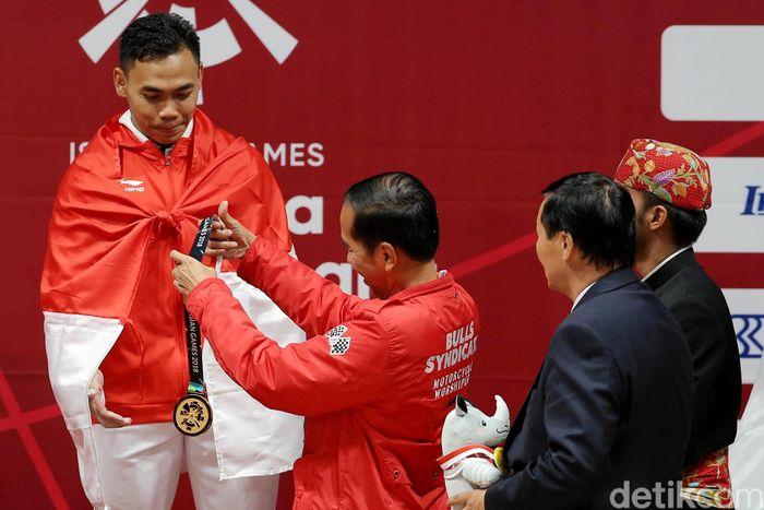 Begini momen saat Jokowi hendak mengalungkan medali emas kepada Eko Yuli Irawan.