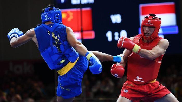 Atlet wushu Puja Riyaya (kiri) dipastikan meraih medali perunggu di nomor sanda putra 70 kg ( Foto: ANTARA FOTO/INASGOC/Akbar Nugroho Gumay/nak/18)