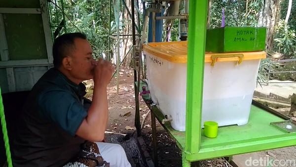 Traveler minum air zam-zam dari Situ Lengkong Panjalu di Ciamis, Jawa Barat. Ada kisahnya mengapa air zam-zam konon tumpah di situ ini. (Dadang/detikTravel)