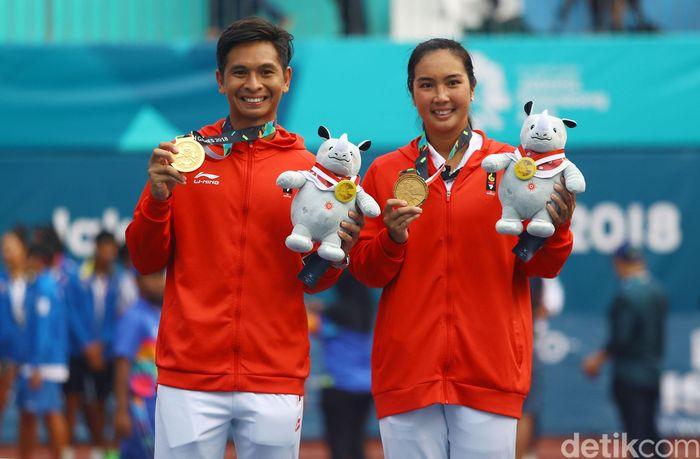 Christopher Rungkat dan Aldila Sutjiadi menunjukkan medali emas yang diraihnya, Sabtu (25/8/2018).