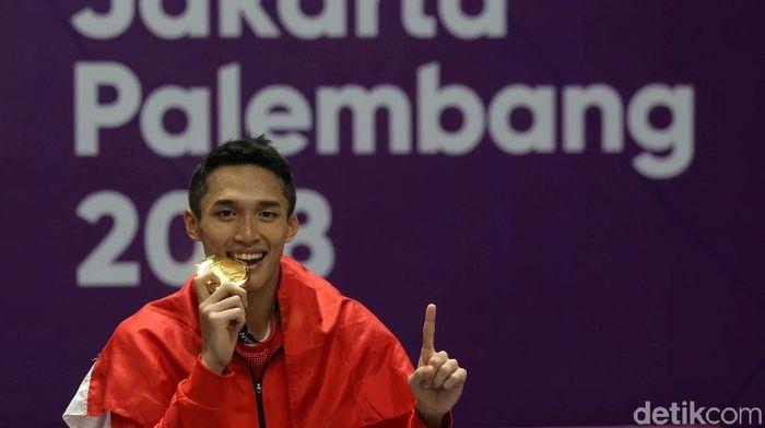 Jonatan Christie menggigit medali emas yang beliau sanggup di Asian Games 2018 (Agung Pambudhy/detikSport)