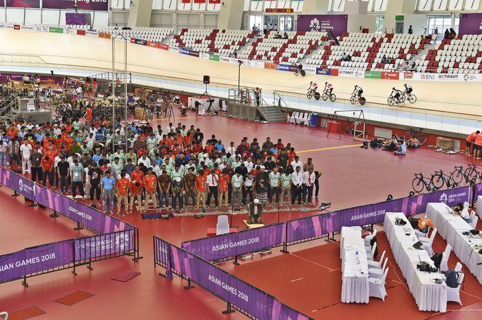 Sejumlah atlet balap sepeda berlatih saat berlangsungnya salat Jumat di dalam track di Velodrome Rawamangun, Jakarta, Jumat (31/8). ANTARA FOTO/INASGOC/Jefri Tarigan.