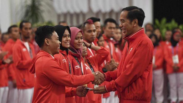 Presiden Joko Widodo (kanan) menyalami dan memberikan buku tabungan kepada lifter Eko Yuli Irawan (kiri) saat pemberian bonus kepada atlet peraih medali di Istana Negara, Jakarta, Minggu (2/9).