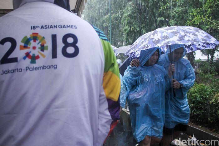 Ribuan penonton yang sudah memadati area nonton bareng di Stadion Gelora Bung Karno (SUGBK), rela hujan-hujanan untuk nonton bareng.
