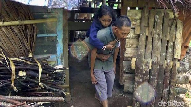 Dasirin saat gendong anaknya, Wiwit yang lumpuh keluar dari kandang kerbau.