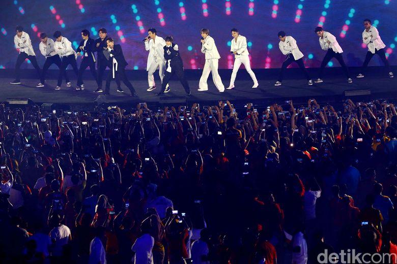 Penonton dibikin riuh saat siluet personel Super Junior muncul di atas panggung.