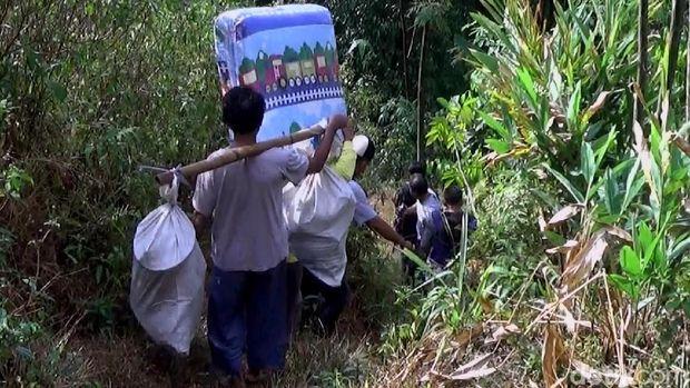 Warga gotong royong membantu evakuasi keluarga Dasirin.