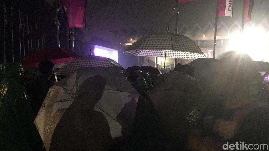 Pakai Jas Hujan dan Payung, Warga Setia Nobar Lewat Layar di GBK