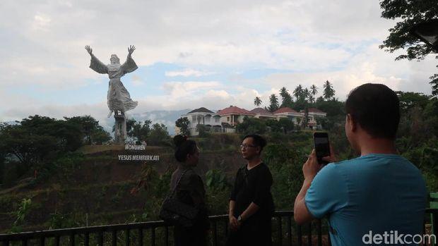 Wisatawan berfoto dengan latar patung Yesus Memberkati (Bonauli/detikTravel)