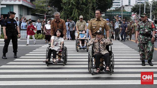 Gubernur DKI Jakarta Anies Baswedan mendorong penyandang disabilitas menyeberang menggunakan pelican crossing di kawasan Bank Indonesia, Jakarta, Selasa (4/9).