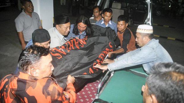 Petugas bersama anggota keluarga memindahkan jenazah korban kecelakaan di Cikidang, Sukabumi, di Rumah Duka Sinar Kasih, Bogor, Jawa Barat, Minggu (9/9).