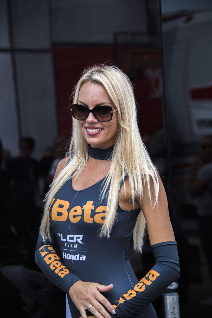 Grid girl tersenyum di depan paddock saat digelar sesi latihan bebas MotoGP San Marino (Mirco Lazzari gp/Getty Images)